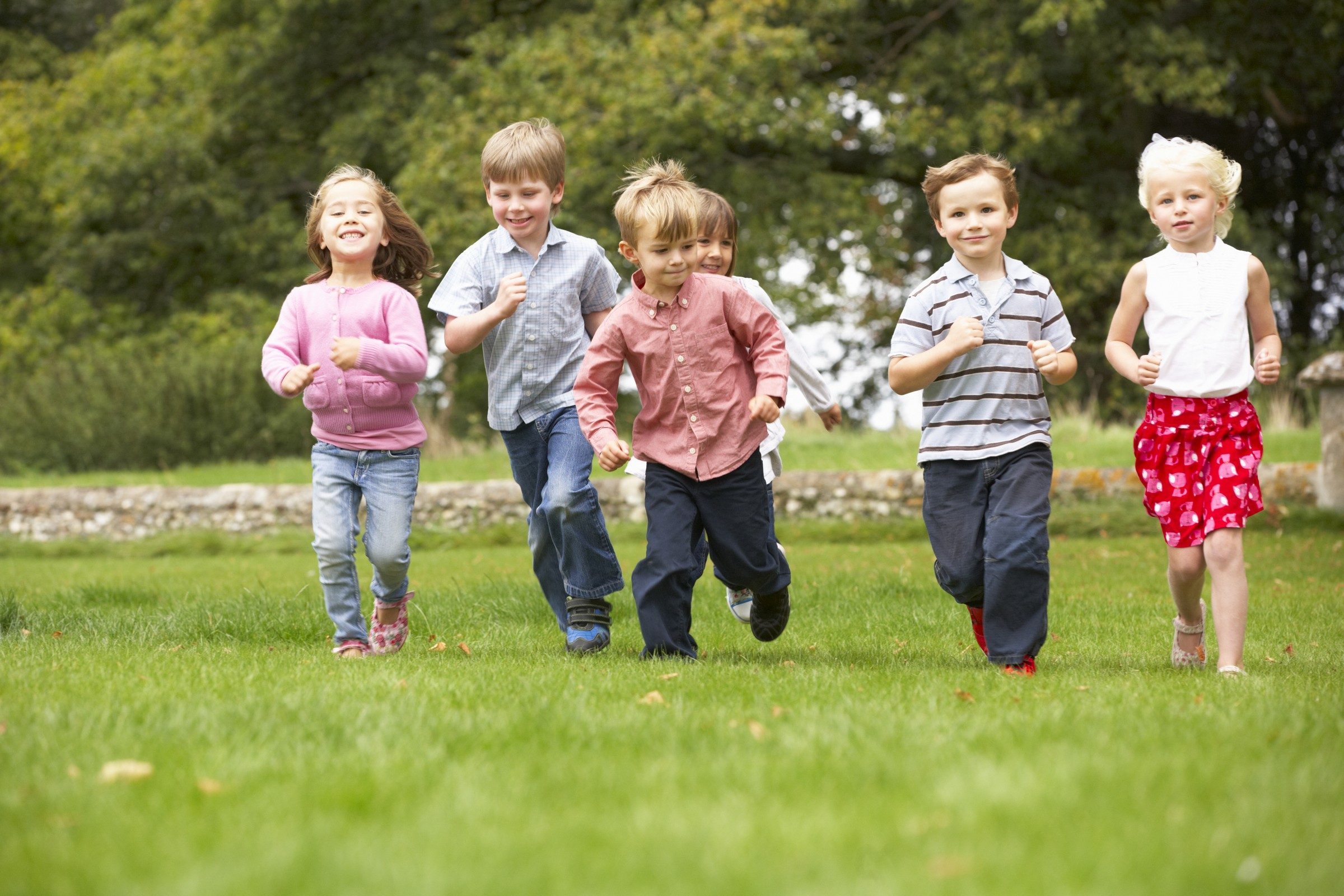Small group young children running in park